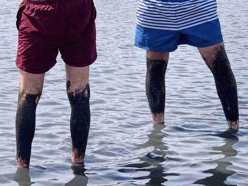 אנשים מרוחים בבוץ בחוף הים של נין. חופשה משפחתית בקרואטיה